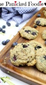 Gluten-free blueberry zucchini cookies sit on a bread board. Blueberries, shredded zucchini, and cookie crumbs are scattered about. A tea towel sits in the background. At the top of the image are the words 'The Panicked Foodie,' with a mixing bowl containing three sugar cubes at the end.