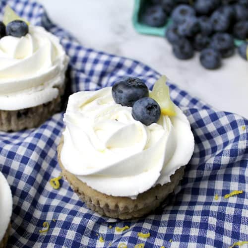 Three vegan blueberry zucchini cupcakes topped with vegan lemon buttercream frosting sit on a tea towel. In the background are blueberries and a lemon. Lemon zest is scattered around the cupcakes.