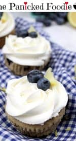 Three vegan blueberry zucchini cupcakes topped with vegan lemon buttercream frosting sit lined up on a tea towel. In the background are blueberries and a lemon. Lemon zest is scattered around the cupcakes. At the top of the image are the words 'The Panicked Foodie,' with a mixing bowl containing three sugar cubes at the end.