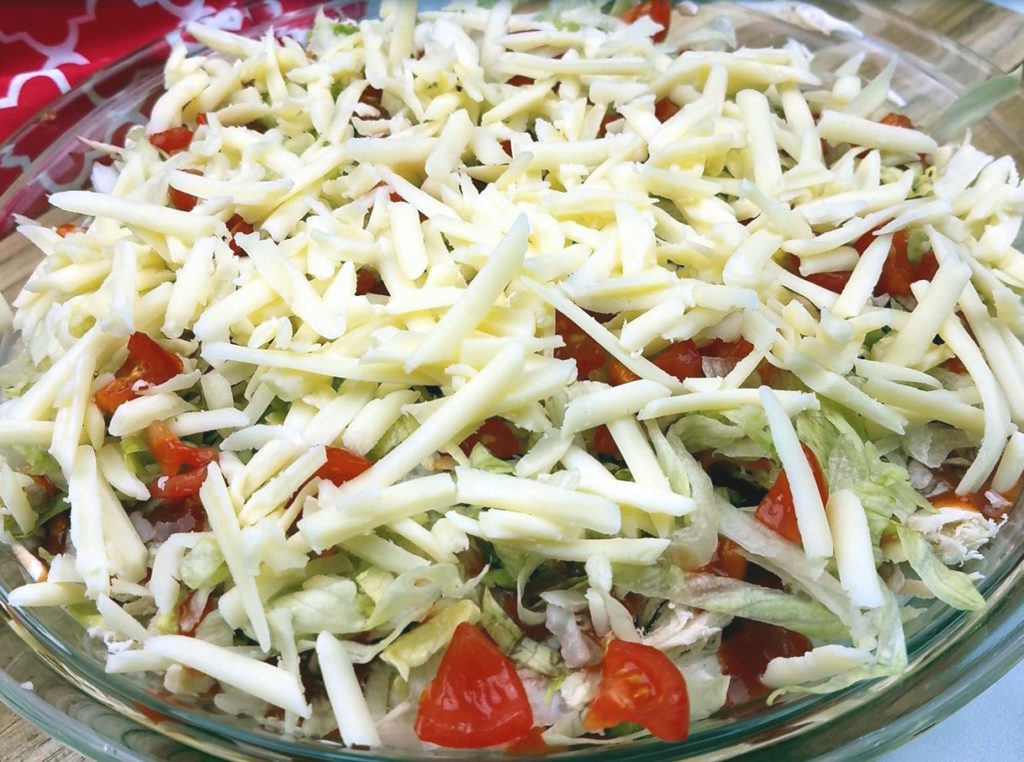 The finished 5 layer taco dip after adding shredded cheddar cheese on top of the shredded lettuce and chopped tomato.