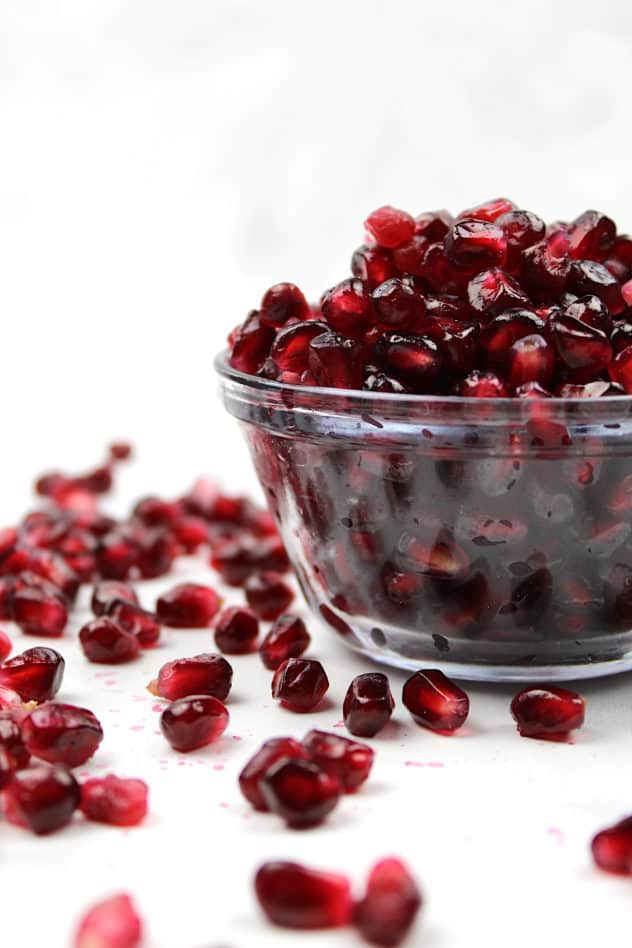 Pomegranate seeds sit in a small bowl, with seeds scattered around.