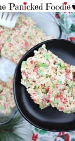 Two rice Krispie treats sit on a plate off to the right. In the background is the pan of rice Krispie treats, a tea towel, and a fake sprig of evergreen. At the top of the image are the words 'The Panicked Foodie,' with a mixing bowl containing three sugar cubes at the end.