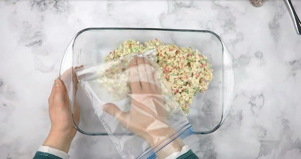 Pressing the rice krispie and marshmallow mixture into the pan with a sandwich baggie covered hand.