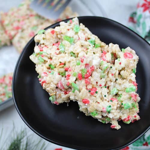 Two rice Krispie treats sit on a plate. In the background is the pan of rice Krispie treats, a tea towel, and a fake sprig of evergreen.